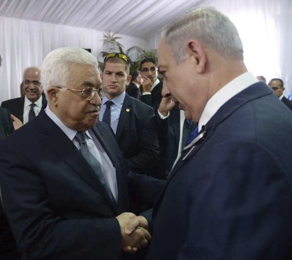 El primer ministro israelí, Benjamin Netanyahu (d) saluda al presidente palestino, Mahmud Abás, durante el funeral.(EFE).