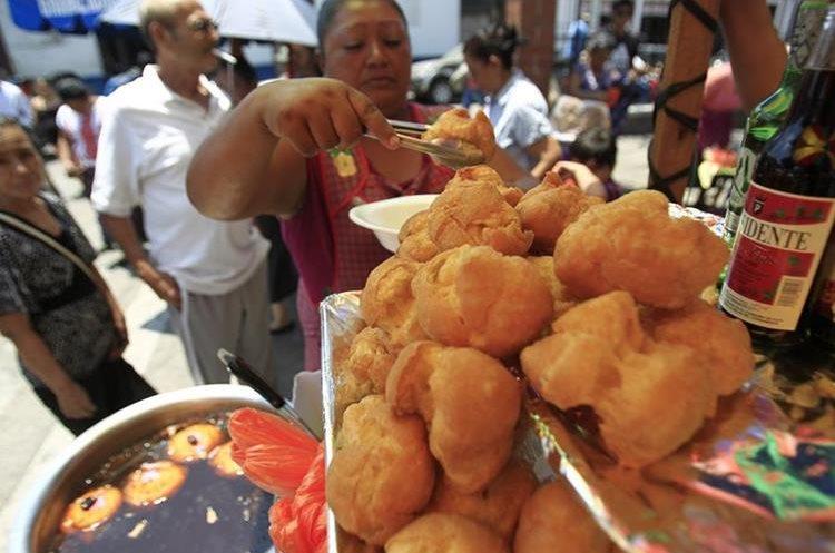 Brenda López despacha una porción de buñuelos. (Foto Prensa Libre: Carlos Hernández).
