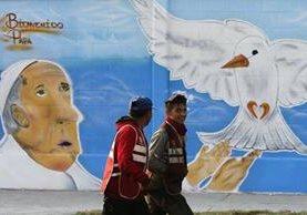Dos jóvenes pasan frente a un grafiti dedicado al papa Francisco en Ecatepec, Ciudad de México. (Foto Prensa Libre: EFE).
