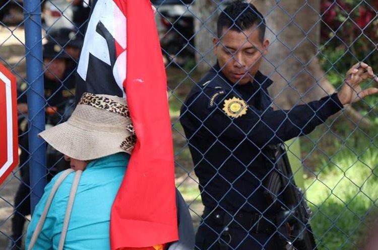 Un agente de la comisaría 33 ve a una salubrista que llegó a respaldarlos el pasado jueves. (Foto Prensa Libre: Cristian Icó)