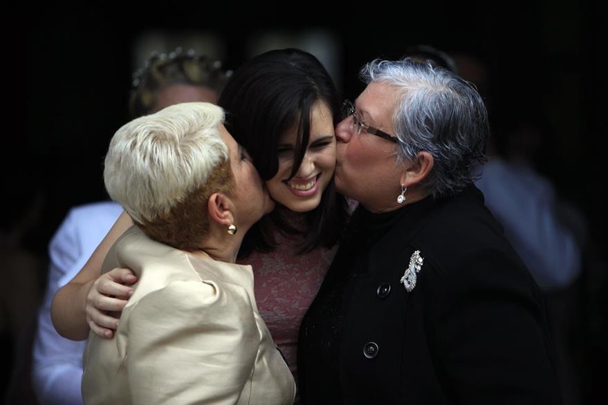 Ada Conde, derecha, e Ivonne Alvarez, izquierda, besan a su hija Adita Alvarez, durante la boda homosexual masiva que tuvo lugar en Puerto Rico. (Foto Prensa Libre: AP).