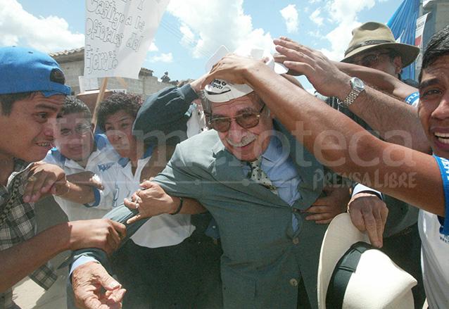 Ríos Montt es resguardado de la lluvia de piedras y palos el 14 de junio de 2003. (Foto: Hemeroteca PL)