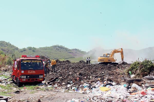 Bomberos Voluntarios  de San Benito apoyan en sofocar un incendio en el basurero municipal. (Foto Prensa Libre: Rigoberto Escobar)