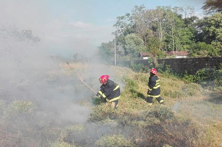 Socorristas utilizan ramas de árboles para sofocar incendios forestales en Malacatán. (Foto Prensa Libre: Whitmer Barrera)
