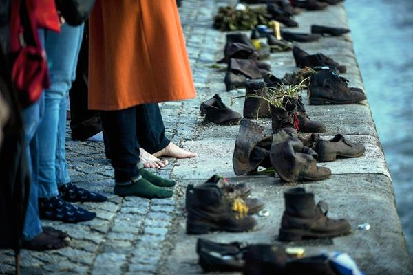 Gitanos tomados de la mano frente al monumento de los zapatos de metal. (Foto Prensa Libre: EFE).