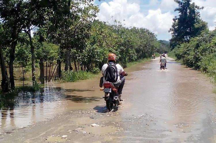 Vecinos atraviesan una calle hacia Creeck Zarco en Morales, Izabal, la cual se inundó la crecida del río Motagua. (Foto Prensa Libre: Dony Stewart)