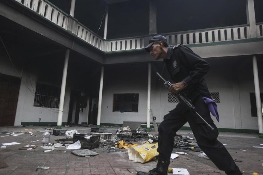 Un policía camina entre los destrozos causados en la comuna por fieles que pedían vivo al párroco. (Foto Prensa Libre: AP).