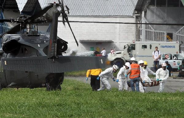 Rescatistas trasladan a un sobreviviente de la tragedia aérea en Colombia.(AFP).