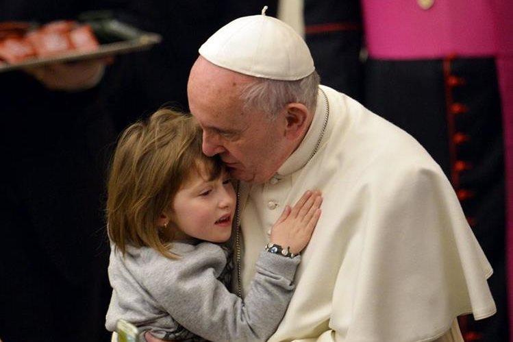 El papa Francisco abraza a una niña en el Vaticano. (Foto Prensa Libre: AFP).
