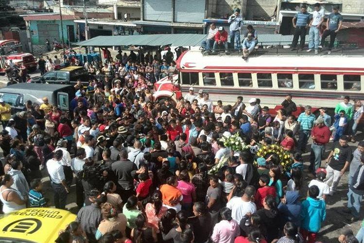 Familiares y amigos del piloto asesinado Walter Paxtor despiden sus restos en la parada de buses en Ciudad Peronia, (Foto Prensa Libre: É. Paredes)