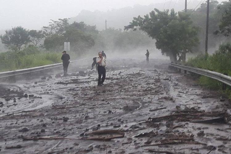 Un lahar bajó desde la barranca Las Lajas y se desbordó sobre la RN-14, en la aldea El Rodeo. Maquinaria pesada trabaja para despejar la vía. (Foto Prensa Libre: PNC)