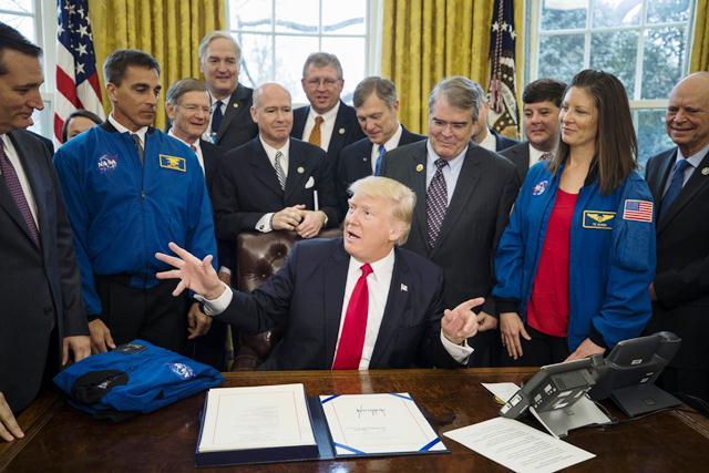 Donald Trump unto a funcionarios de la NASA en la firma de la ley que aprueba fondos. (Foto Prensa Libre: EFE)