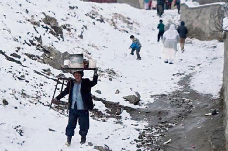 Un vendedor  ambulante afgano transporta sobre su cabeza una olla después de una nevada, en Kabul.