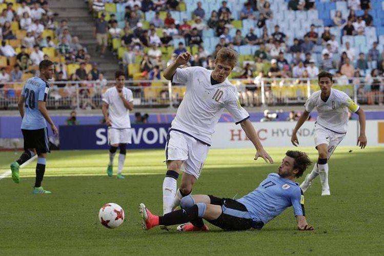 El italiano Luca Vido, trata de quedarse con el balón tras la barrida del uruguayo Matias Vina. (Foto Prensa Libre: AP)