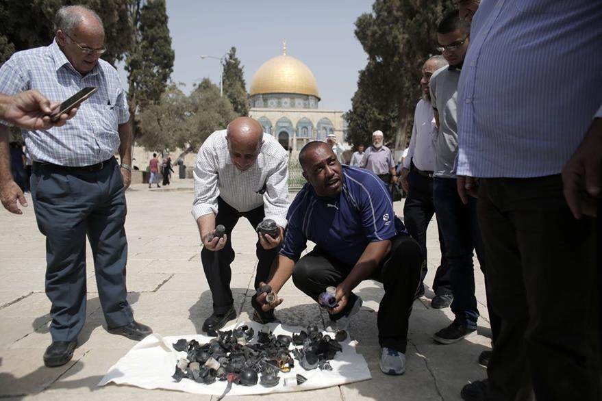 Palestinos muestran las artefactos usados por policías israelíes. (AFP)
