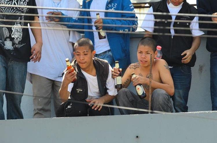 Luego de caer dentro de una bodega de cervezas los internos repartieron botellas mientras seguían en los techos. (Foto Prensa Libre: Estuardo Paredes)