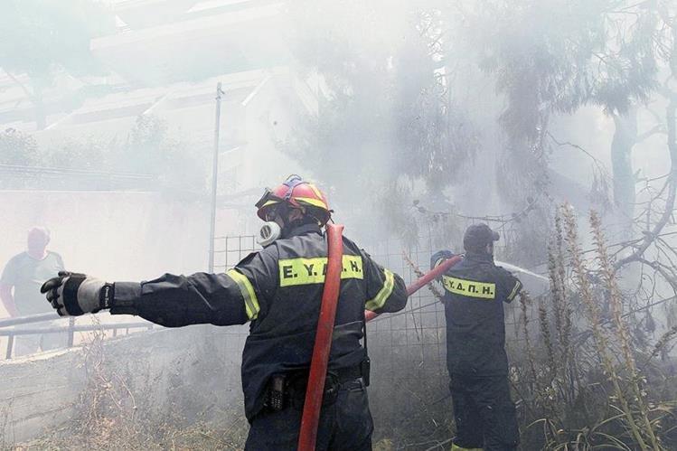 Los bomberos intentan extinguir las llamas en el suburbio de Karea en Atenas,Grecia. (Foto Prensa Libre:EFE)