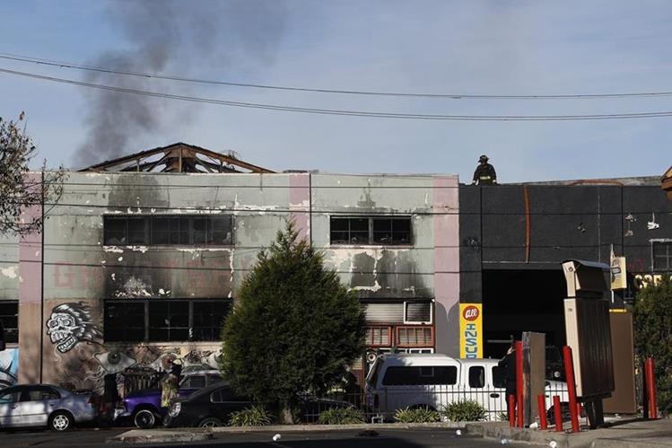 Un bombero observa la parte superior del edificio (aún humeante) donde murió la mayoría de víctimas. (Foto Prensa Libre: EFE).
