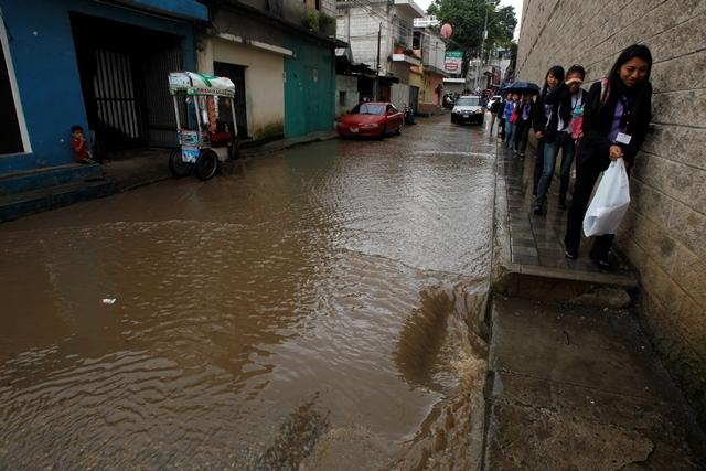 Estudiantes en Boca del Monte tienen dificultades para cruzar calles por inundaciones. (Foto Prensa Libre: Paulo Raquec)