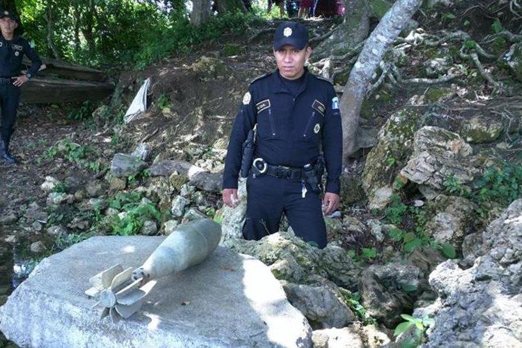 Agente de la PNC observa explosivo localizado en Sayaxché. (Foto Prensa Libre: Rigoberto Escobar).