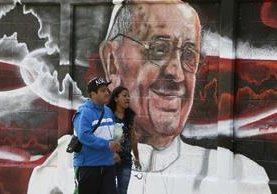 Una pareja camina junto a un mural del papa Francisco pintado por jóvenes en Ecatepec, México.