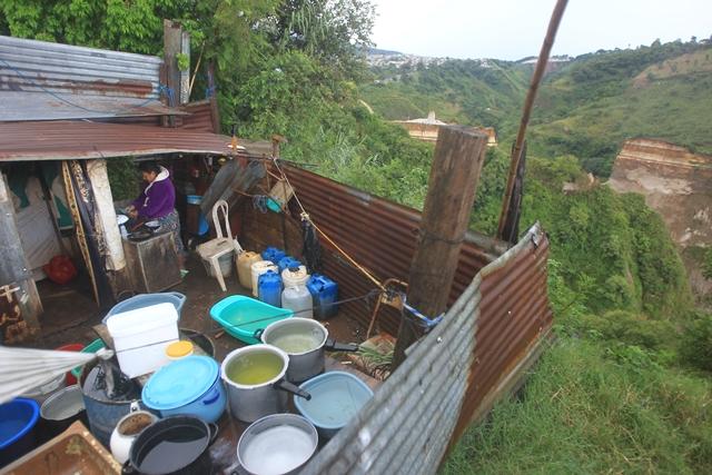 Lucrecia Hernández, de 60 años, es madre soltera y cocina el almuerzo para sus tres hijos y dos nietos. La vivienda se ubica en la ladera de un barranco en el asentamiento Regalito de Dios, zona 8 de Villa Nueva. (Foto Prensa Libre: Esbin García)