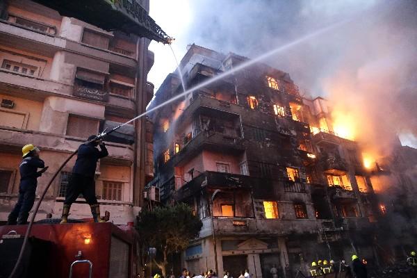 Bomberos extinguen el fuego en la zona de un centro comercial en El Cairo. (AFP)