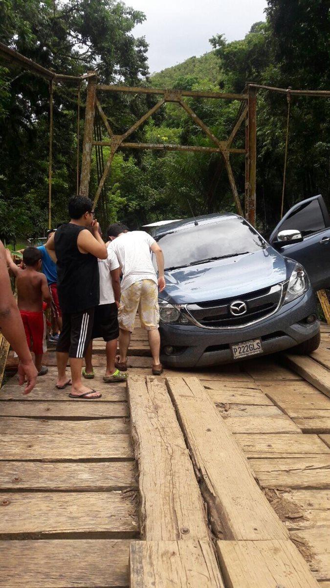 Pobladores ayudan al dueño de vehículo a destrabarlo de entre los tablones del puente que se halla a un kilómetro de Semuc Champey, Lanquín. (Foto Prensa Libre: Eduardo Sam Chun)