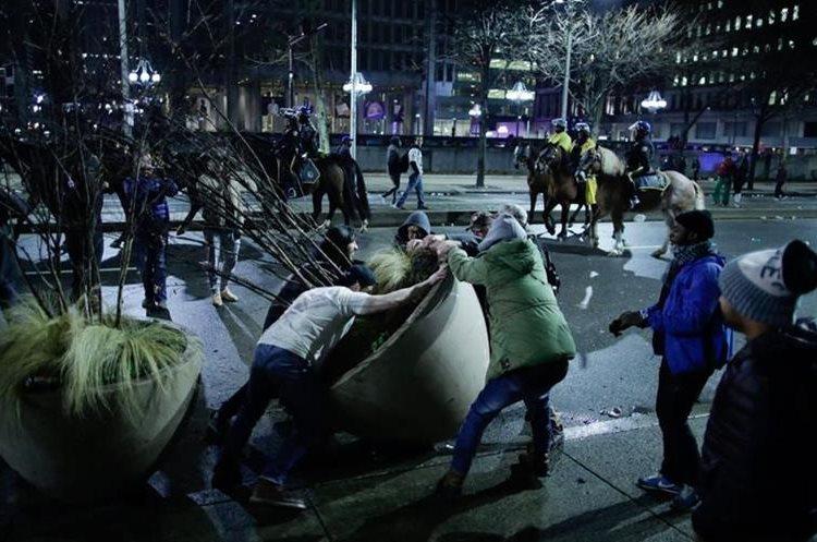 Un grupo de manifestantes violentos intentan destruir parte del jardín de la ciudad de Filadelfia. (Foto Prensa Libre: AFP).