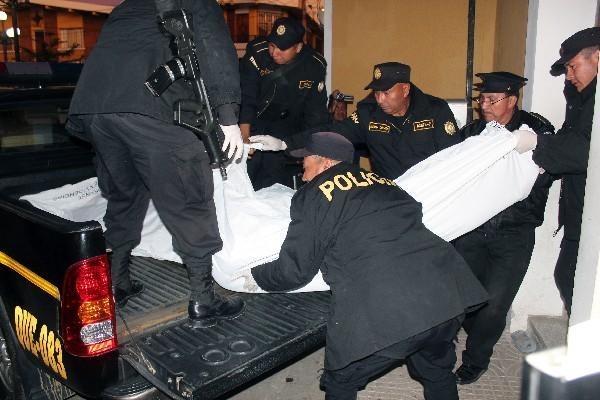 Agentes de la PNC suben en la palangana de un autopatrulla a uno de sus compañeros asesinados en junio del 2013, en la estación de Salcajá.
