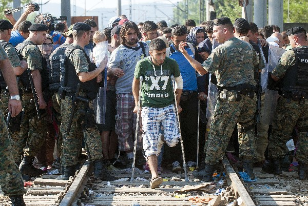 Policía macedonia permiten a los migrantes a cruzar una línea fronteriza.