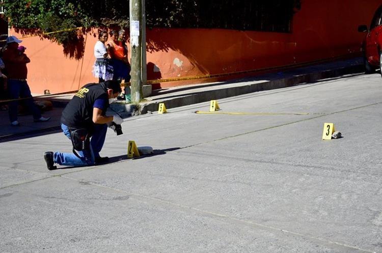 Un investigador del MP recolecta evidencias en el donde fue baleado el comerciante en Huehuetenango. (Foto Prensa Libre: Mike Castillo)