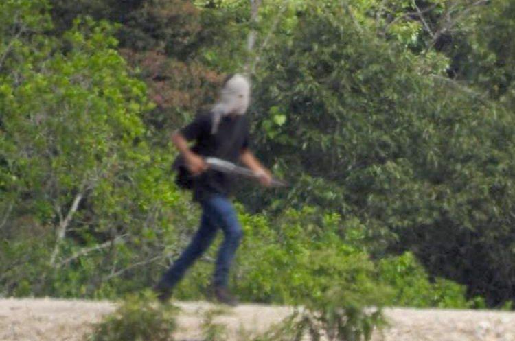 Un manifestante con un arma se desplaza en la Franja Transversal del Norte, en Ixquisis, San Mateo Ixtatán. (Foto Prensa Libre).