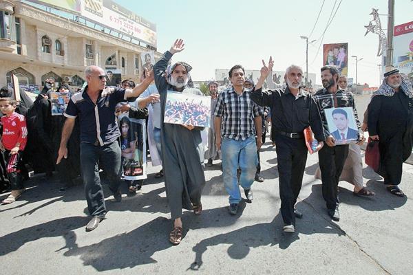 Varias personas sostienen fotografías de sus familiares, que se cree fueron asesinados por el Estado Islámico. (Foto Prensa Libre:EFE)