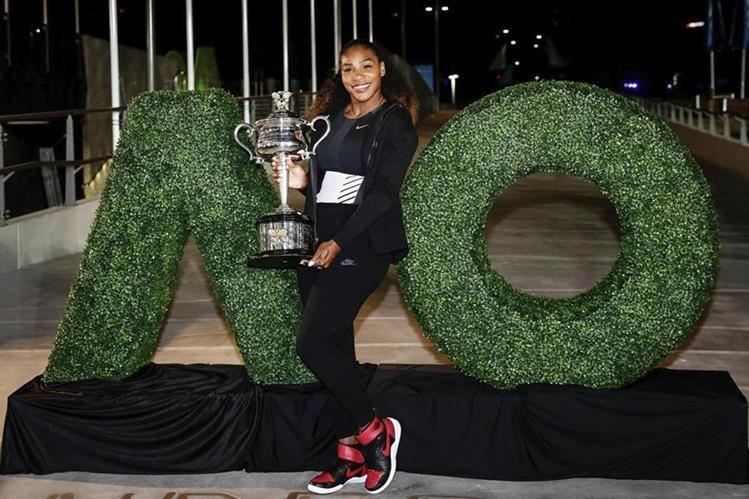 La tenista estadounidense Serena Williams posa y sonríe con el trofeo del Australia Open obtenido el fin de semana frente a su hermana Venus. (Foto Prensa Libre: EFE)