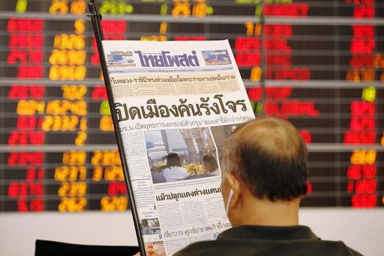 Un inversionistas ve el diario frente a indicadores de la bolsa de Tailandia. (Prensa Libre- EFE)