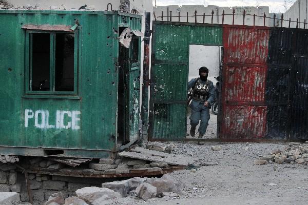 Un agente de seguridad afgano inspecciona daños después de los enfrentamientos.