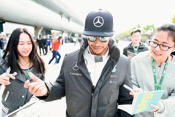 Lewis Hamilton firma autógrafos a sus seguidoras tras la segunda practica del GP de China. (Foto Prensa Libre: AFP).