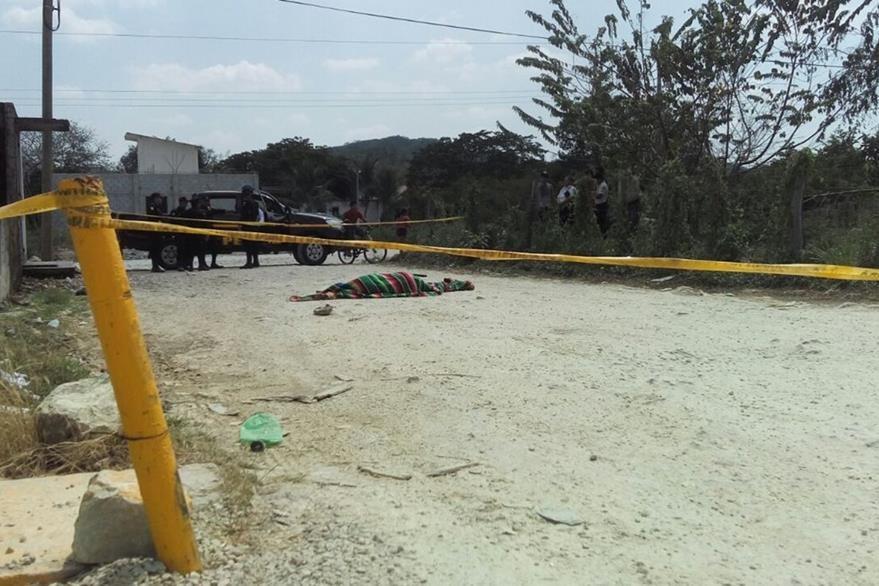 Cadáver de Israel Jacoj  Nazarene es resguardado por agentes de la PNC en Santa Elena, Flores. (Foto Prensa Libre: Manuel Romero)