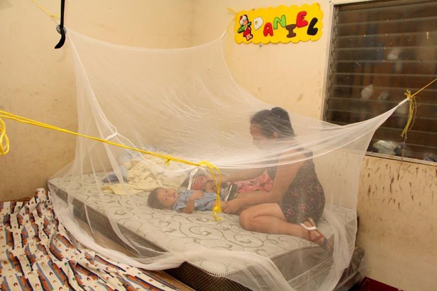 Una madre protege a su hijo con un pabellón, para evitar picaduras de zancudos, en Retalhuleu. (Foto Prensa Libre: Rolando Miranda)
