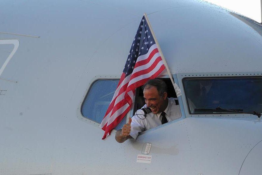 Un integrante de la tripulación saluda al arriba a Cuba. (Foto Prensa Libre: AFP).