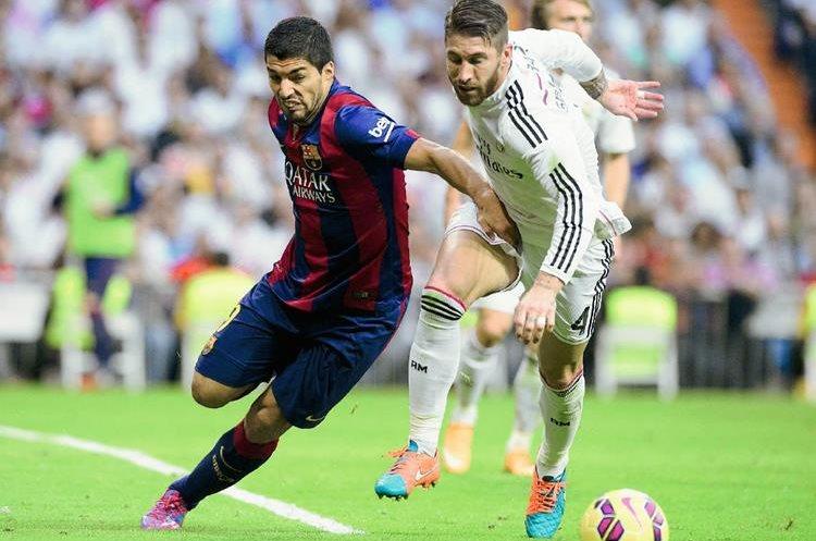 El uruguayo Luis Suárez, pelea el balón con Sergio Ramos en el pasado clásico (Foto Prensa Libre: AFP)