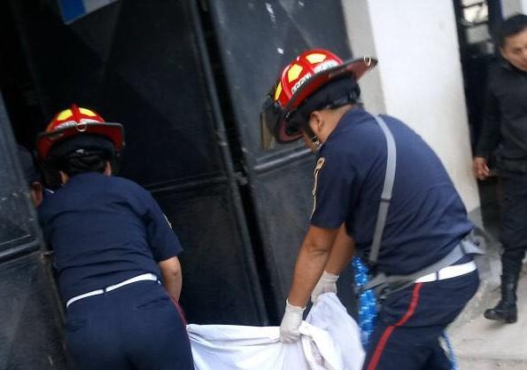 Bomberos trasladan uno de los cadáveres. (Foto Prensa Libre: Eduardo Sam).
