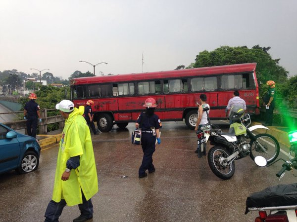 El autobús quedó atravesado en el puente. En el derrape golpeó a un automóvil. (Foto Prensa Libre: Bomberos Municipales)