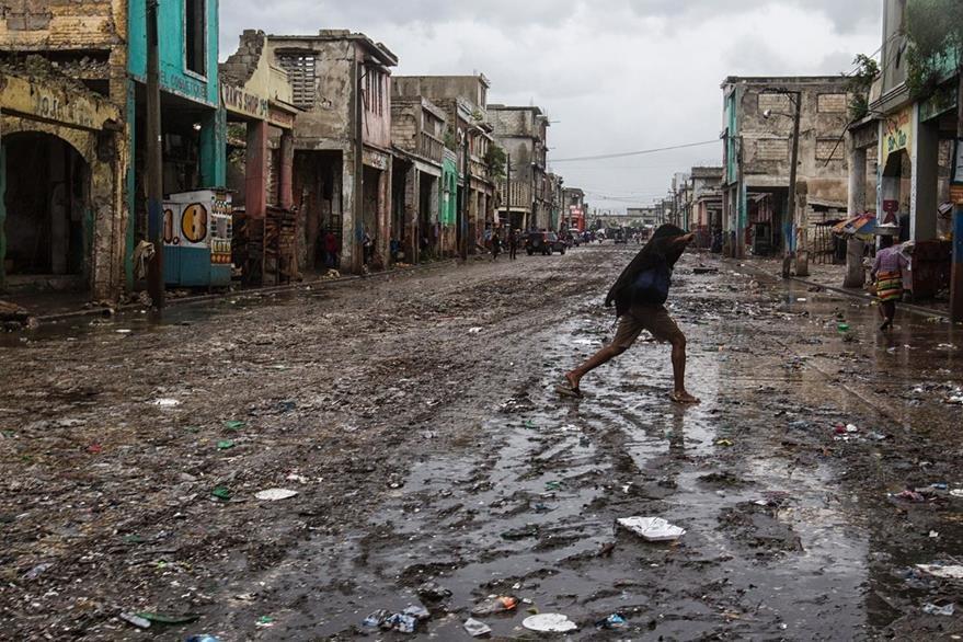 Un hombre corre en medio de una calle devastada en Puerto Príncipe, la capital de Haití. (Foto Prensa Libre: AFP).