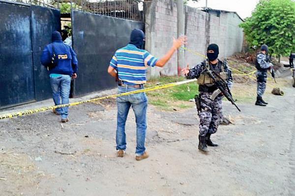 Policías vigilan el lugar donde ocurrió la masacre. (Foto Prensa Libre: Óscar Machón, El Mundo).