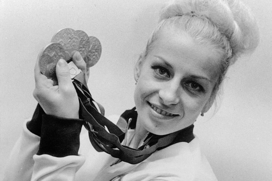 FILE - In this Oct., 1968, file photo, Vera Caslavska of Czechoslovakia holds her four Olympic medals, three gold and one silver which she won in the gymnastics competition. Caslavska, multiple Olympic gold medalist in gymnastics and the most famous Czech sports woman of all times who stood up against the 1968 Soviet-led invasion of Czechoslovakia has died, in Prague, she was 74. (AP Photo, File)