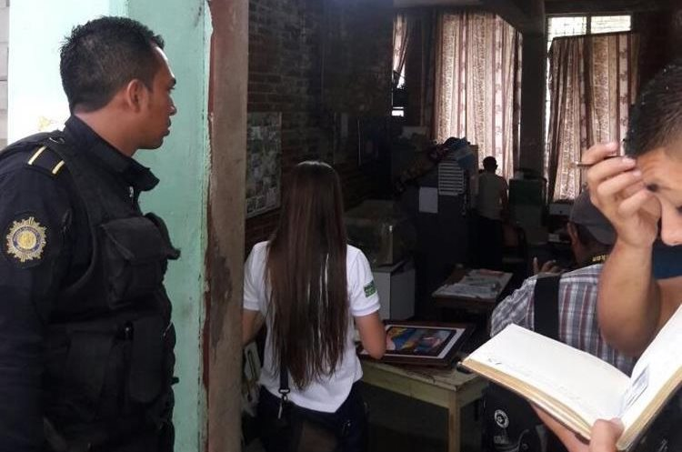 Policías y docentes revisan el área de audio y televisión a donde ingresaron los ladrones.(Foto Prensa Libre: Mario Morales)