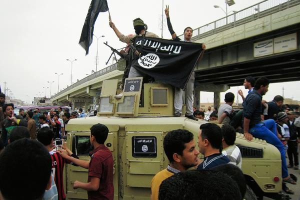 Combatientes del Estado Islámico ondean banderas en un vehículo militar iraquí en Faluya, Irak. (Foto Prensa LIbre:AP)