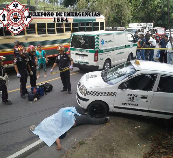 El cuerpo de la víctima yace al lado del taxi que conducía. (Foto Prensa Libre: Bomberos Municipales Departamentales)